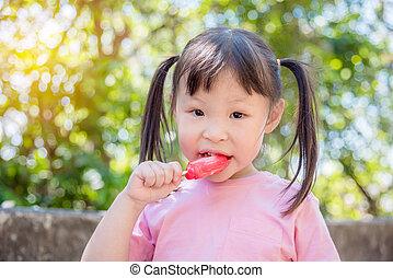 Little asian girl eating ice cream in park