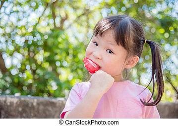 girl eating icecream in park