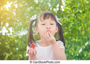 girl eating strawberry between picnic in park
