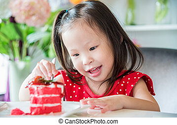 girl eating strawberry cake at home