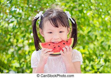 girl eating watemelon between picnic in park