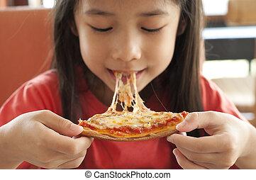 Little Asian girl enjoy pizza.
