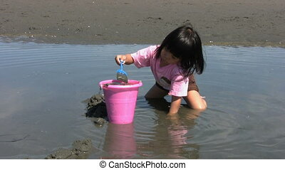 Little Asian Girl Filling A Bucket
