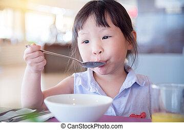 girl having breakfast by herself