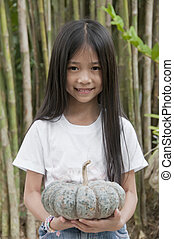 Little Asian girl holding pumpkin.
