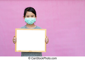 Little asian girl in a protective medical mask holding whiteboard isolated on pink background. Protect from Coronavirus or Covid-19 epidemic.