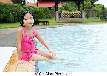 Little Asian girl in swimming pool