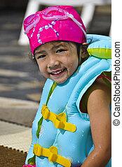 Little Asian girl in swimsuit.