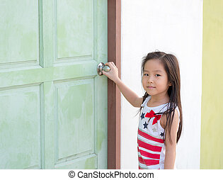 Little Asian girl kid try to open the door