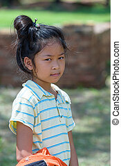 little asian girl look at right side while she in outdoor park.