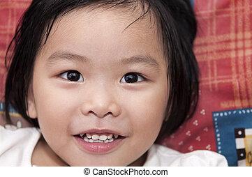 Little Asian girl lying on bed