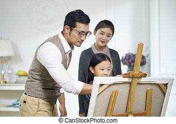 little asian girl making a painting with parents watching and helping