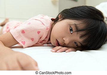 Little Asian girl on bed