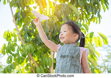 girl playing paper airplane in park