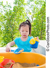 girl playing sand in sand box