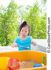 girl playing sand in sandbox