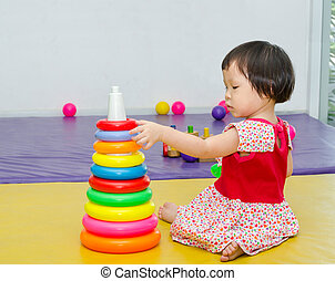 girl playing toy on the floor