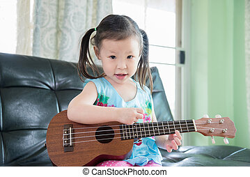 girl playing ukulele at home