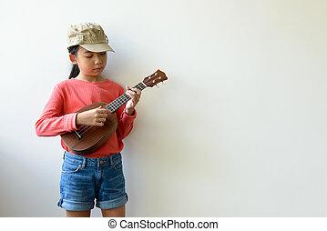 Little Asian girl playing ukulele