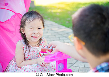 Little asian girl playing with her brother in park