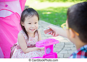 girl playing with her brother in park