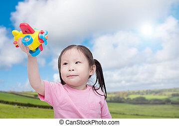 girl playing with plastic plane