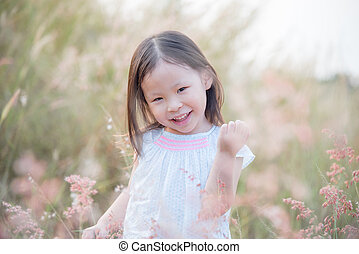 girl playing with wild flower in field