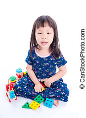 Little asian girl playing with wooden train toy over white