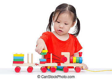 girl playing with wooden train toy