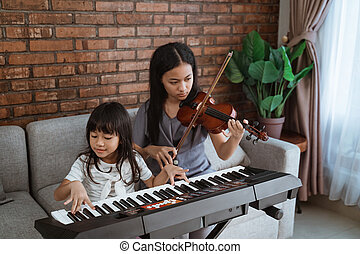 Little asian girl plays a musical instrument keyboard with her sister playing the violin together
