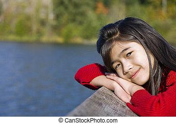 Little asian girl relaxing by lake