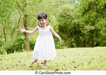 Little Asian girl running at park