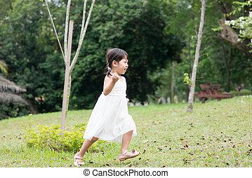 Little Asian girl running outdoors