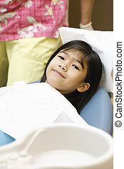 Little Asian girl sitting in dentist's chair ready for cleaning