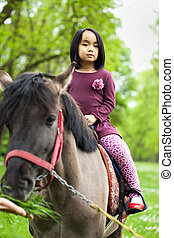 Little Asian girl sitting on a horse