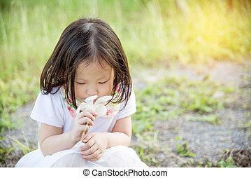 girl smelling flower in park