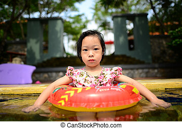 little Asian girl swims in a pool in an orange life preserver.