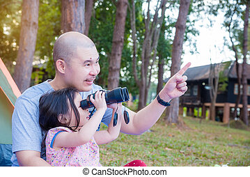 girl using binoculars with her father