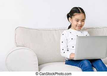Little asian girl with laptop computer or notebook in living rome at home. Learning concept. Shopping online concept.
