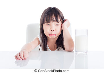 Little asian girl with unhappy face looking at a glass of milk isolated over white background