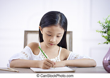 little asian girl writing or drawing
