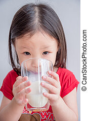 Little asian gril drinking milk from glass - gril drinking...
