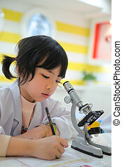 Little Asian kid writing report after looking into microscope