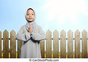 Little asian muslim child with hijab praying