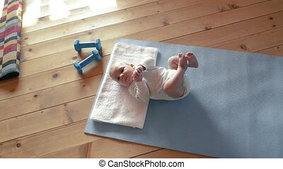 Little baby boy at home lying on exercise mat.