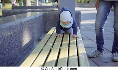 Little baby boy crawling on bench in the park. Outdoor.