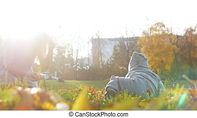 Little baby boy crawling on the grass in the park, smiling. Sunlight.