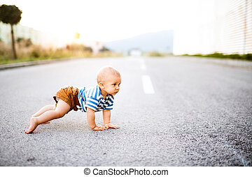 Little baby boy crawling outside on the road.