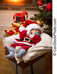 baby boy in Santa costume sleeping on Christmas night at living room