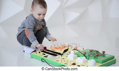 Little baby boy intently playing with busy board